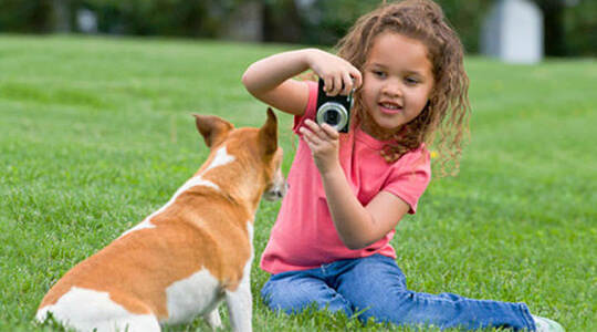 Girl taking photo of dog